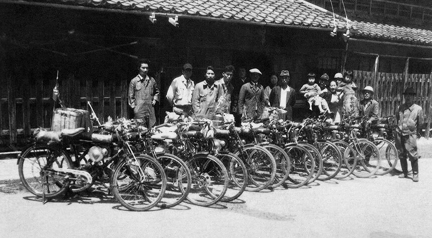 The image depicts the era of Honda in 1952 where Honda motor bike were used for transportation