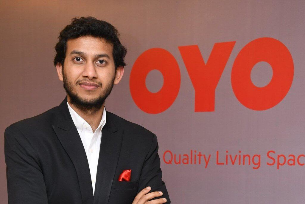 Ritesh-Agarwal-possing-with-oyo-rooms-logo-a-successful-startup